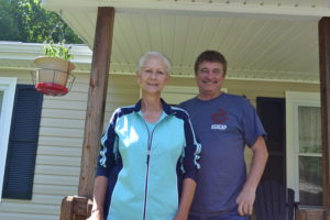 Peggy Wolford of Leander stands on her porch with Big Sandy Area Community Action Program Weatherization Assistance Program Inspector Steve Mullins. Mullins and the BSACAP added insulation to Wolford's home free of charge in order to help her manage her winter heating bills.